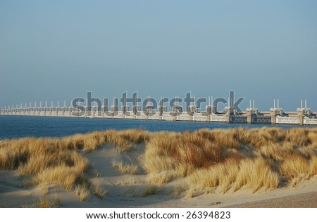 Dutch dike with  wind drifted dunes and at the back the oosterschelde flood barrier protecting the low land against disasters in case of storm surges - stock photo