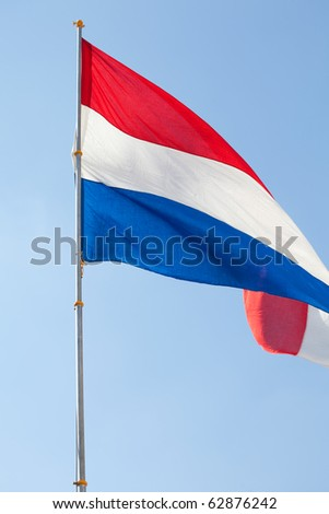 Dutch flag against the blue sky - stock photo