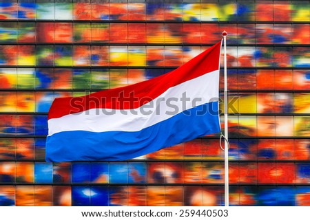 dutch flag in front of colorfull facade - stock photo