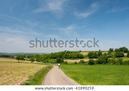 Dutch landscape in limburg with bikers on the road stock photo
