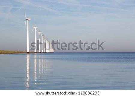 Dutch offshore wind turbines in a calm sea - stock photo