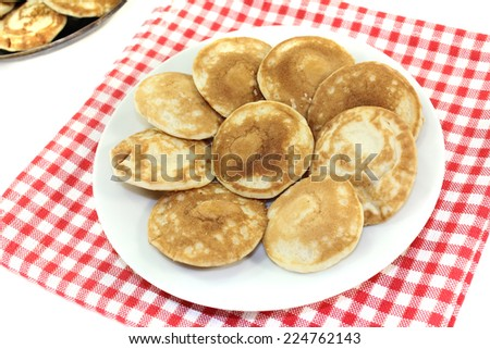 Dutch Poffertjes on a plate with napkin before light background - stock photo
