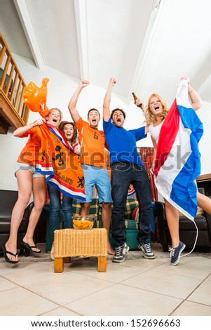 Dutch Sports fans cheer ecstatically over a goal and victory of the national team of the Netherlands at home, watching television with snacks and beer, dressed up in the national color, Orange - stock photo