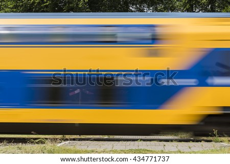 Dutch train passing by on a railway crossing near Ellecom in the Netherlands - stock photo