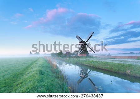 Dutch windmill by river at sunrise, Holland - stock photo