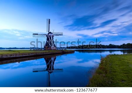 Dutch windmill in dusk by lake, Groningen, Netherlands - stock photo