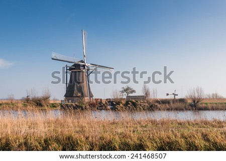 Dutch windmill next to a canal on a sunny day in springtime. - stock photo