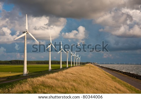 Dutch Windturbines and a cloudscape in the last sunlight of a summer evening - stock photo