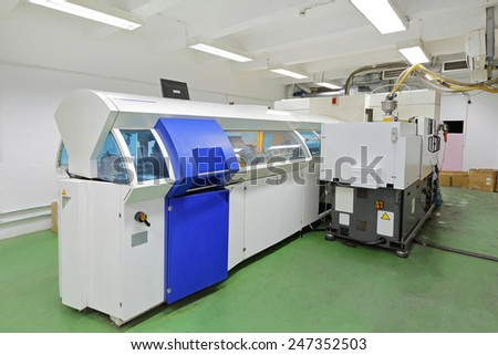 DVD and compact disc manufacturing machine in factory - stock photo