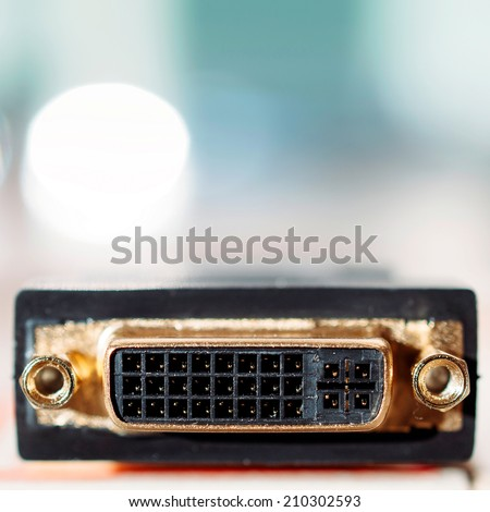 DVI digital video interface PC input cable connector on defocused turquoise background - tilt-shift lens used to accent the connection pins and to emphasize the attention on them - stock photo
