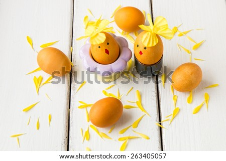Dyed natural way with turmeric for mustard - yellow color Easter eggs decorated as chicken couple. - stock photo