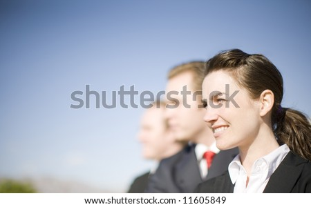 Dynamic group of business leaders standing together facing the same direction - stock photo