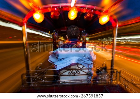 Dynamic perspective and long time exposure inside a Tuk tuk vehicle in Bangkok, Thailand - stock photo