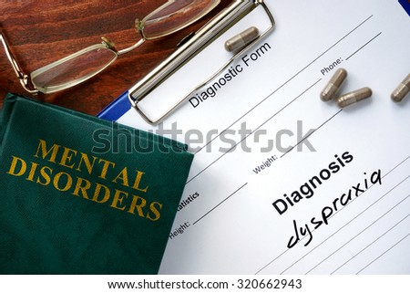 Dyspraxia  concept. Diagnostic form and book on a table. - stock photo