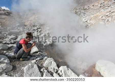 DZENZUR VOLCANO, KAMCHATKA, RUSSIA - SEP 04, 2014: Beautiful girl photographing the steaming (smoking) fumarole on crater active Dzenzur Volcano on a sunny day. Eurasia, Russian Far East, Kamchatka. - stock photo