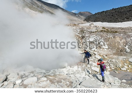 DZENZUR VOLCANO, KAMCHATKA, RUSSIA - SEPTEMBER 04, 2014: Tourists standing by smoking fumaroles on the crater active Dzenzur Volcano on a sunny day. Eurasia, Russia, Far East, Kamchatka Peninsula. - stock photo