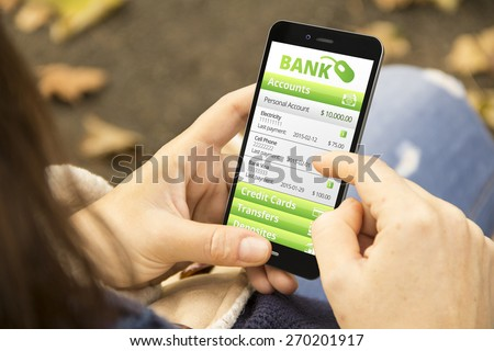 e-banking concept: young woman with online bank application phone at the park - stock photo