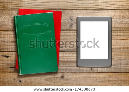 E-book reader and books on wooden background - stock photo