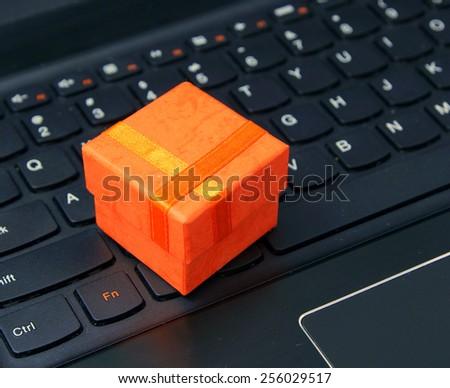 e-commerce and web shopping: orange present case on the laptop keyboard - stock photo