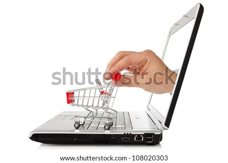 e-commerce concept. hand reaches out of a laptop with a shopping cart - stock photo
