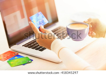 E-commerce concept. Woman with credit card, laptop and cup of coffee, close up - stock photo