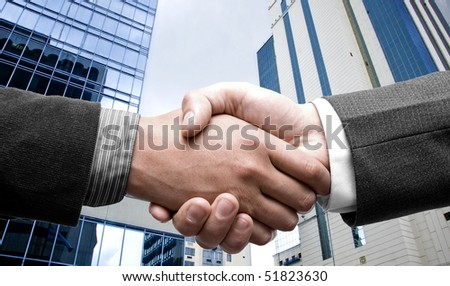 e-commerce handshake and business city buildings in the background - stock photo