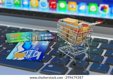 E-commerce, online purchases and internet shopping concept, shopping cart with cardboard boxes and credit cards on laptop keyboard - stock photo