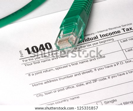 E-File Taxes - A 1040 tax form and network cable. Electronic Filing (E-File) concepts. The year on the form is hidden by the network cable to add to the image usefulness. - stock photo