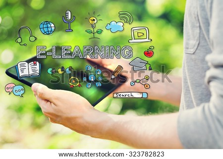 E-Learning concept with young man holding his tablet computer outside in the park  - stock photo