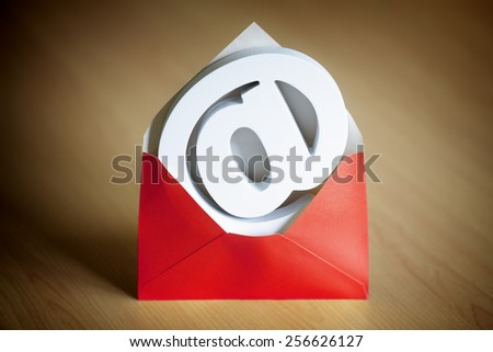 E-mail at symbol inside a red envelope on a desk  - stock photo