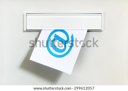 E-mail symbol on letter being delivered through a letterbox concept for internet communication, social media and contact us - stock photo