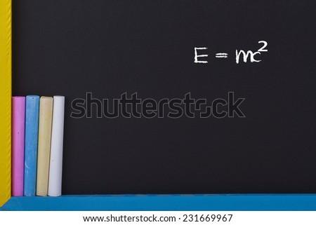 E=mc²  Physical Formula on Blackboard with Colourful Chalks - stock photo
