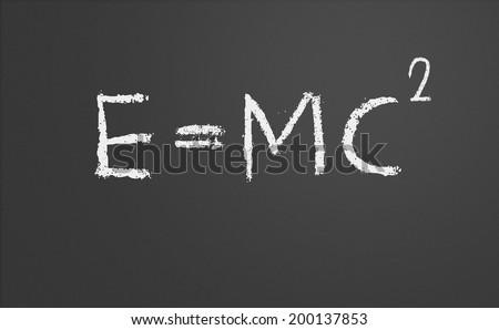 E=mc2. Theory of relativity written on a chalkboard - stock photo