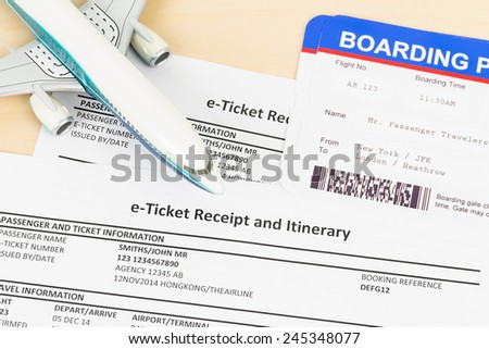 E-ticket with plane model, and boarding pass - stock photo