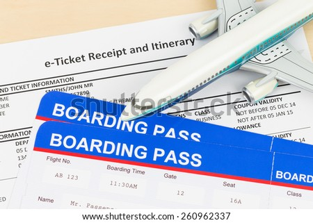 E-ticket with plane model, and boarding pass; ticket and boarding pass are mock-up - stock photo