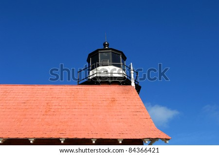"""Eagle Harbor Lighthouse is an historic landmark in Upper Peninsula, Michigan on Lake Superior.  Rooftop and nest is shown including the """"EH"""" etched on outside of glass top. - stock photo"""