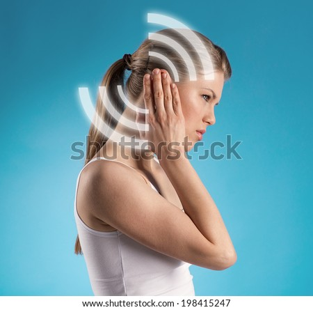 Ear therapy. Stressed girl suffering from noise. - stock photo