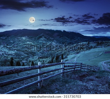 early autumn landscape. fence on the agricultural meadow near path on the hillside. forest in fog on the mountain at night in full moon light - stock photo