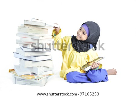 Early education with cute Muslim girl reading and choosing stacks of books in isolated white background. - stock photo