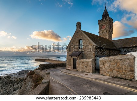 Early evening at the old clock tower at Porthleven a small fsihing town in Cornwall - stock photo