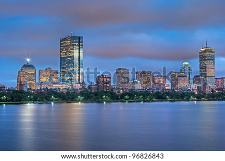 Early Evening View of the Boston Skyline with brightly illuminated buildings - stock photo