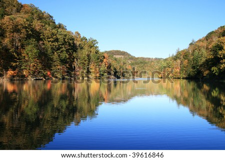 early fall reflection in Mill Creek Lake, Natural Bridge State Park, Kentucky with the leaves just starting to change color - stock photo