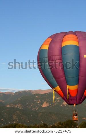 Early morning hot air balloon with Colorado Rockies as backdrop - stock photo