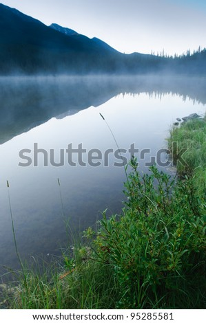 Early morning mist in scenic rocky mountains - stock photo