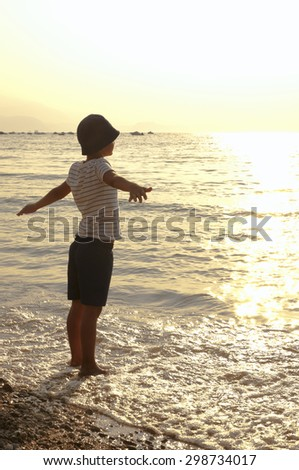 early morning on the sea child arms outstretched basking in the sun - stock photo