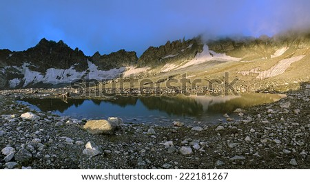 Early morning panorama of small moraine lake at an altitude of 3400 meters near the South Belag Pass in Digoria, Caucasus, Republic of North Ossetia-Alania, Russia - stock photo