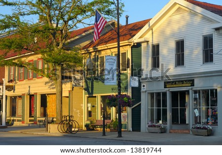 Early morning sunlight on businesses of a quaint village main street - stock photo