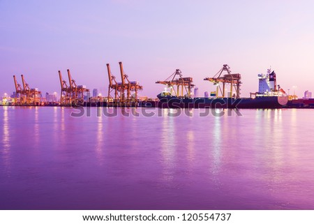 early morning twilight at industrial cargo harbor along river - stock photo