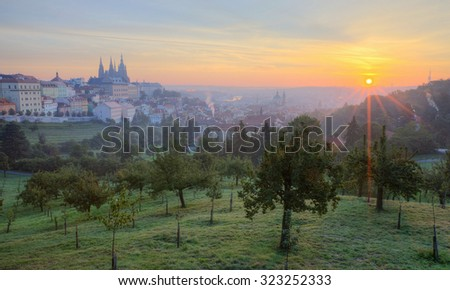 Early morning view of misty Prague with golden sunrise ~ A panorama over Prague Old Town with majestic Prague Castle and St. Vitus Cathedral on the left and the golden rising sun in the background - stock photo