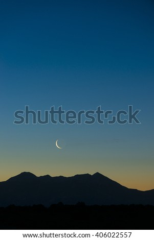 Early morning waning waxing crescent moon rising over graphic silhouetted mountain vertical - stock photo